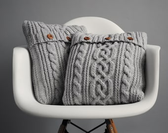Light grey cable knit pillow cover with 3 wooden buttons.