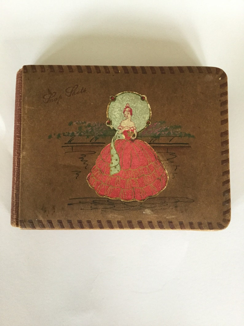 Antique Vintage old Leather Photo Album with Crinoline Lady Doll Sticker and the words Snap Shots on the front