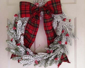 Red and White Flocked Christmas Wreath. Snowy Faux Greens and Red Berries on a Red Painted Grapevine Wreath. Large Red Plaid Flannel Bow.