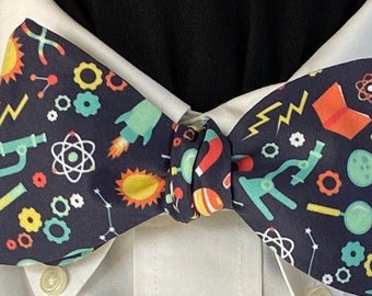 SCIENCE RULES: Organic Cotton Bow Tie, microscopes, rockets, DNA, test tubes, atoms, and more-scattered on a dark blue background