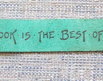 Hand made green leather   bookmark with the message A Good Book Is The Best Of Friends