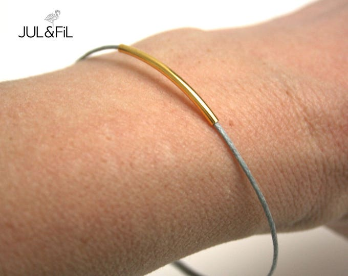 Golden brass tube bracelet with fine gold and pearl grey waxed cotton, smooth graphic tube
