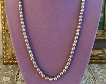 """One unique tribal stamped sterling silver bead resides among the 5 mm round sterling silver beads in this classic 20"""" necklace"""