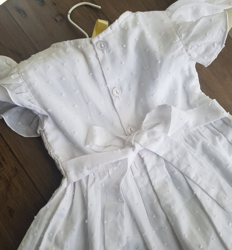 Beautiful spot white hand smocked and embroidered baby dress