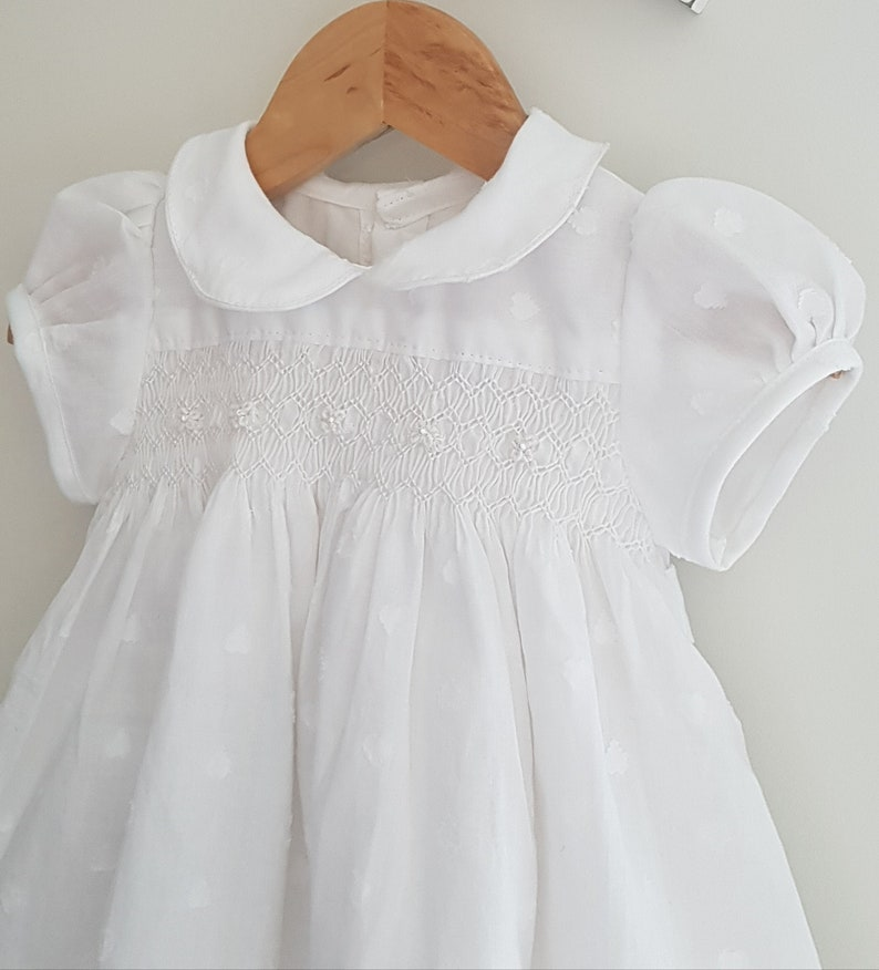 Gorgeous white hand smocked baby dress with elegant hand embroidered detail