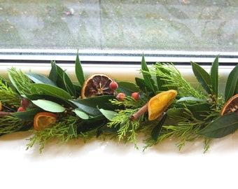 Fresh Christmas garland, mantlepiece. scented dried oranges, Bay leaves, evergreen fir, red berries, cinnamon sticks. Smells divine!