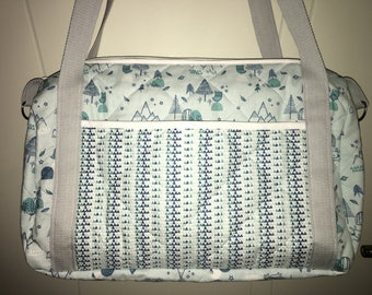 Quilted fabric forest pattern diaper bag.