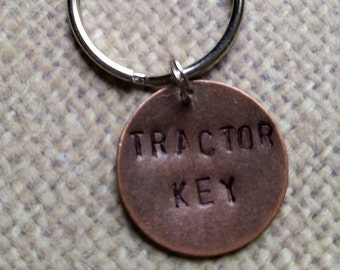 """Keychain hand stamped with """"Tractor Key""""."""