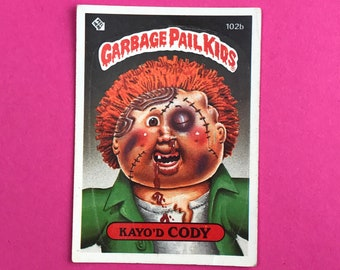 Garbage Pail Kids Sticker Card - KAYO'D CODY 102b - Wanted Poster Back - 1986 Topps Trading Card - 1980's GPK Pop Culture - 80's Gag Gift