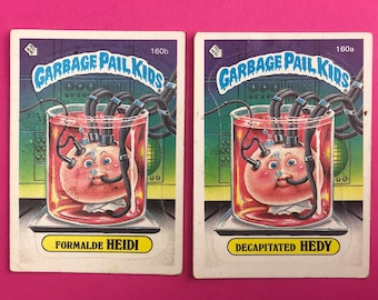 2 Garbage Pail Kids Sticker Cards - Decapitated Hedy 160a & Formalde Heidi 160b - Wanted Poster Back - 1986 Topps Cards - Alternate Name Set
