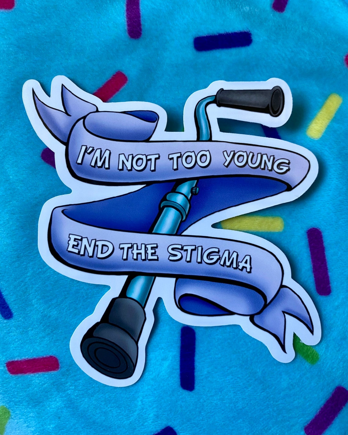 """Sticker of a cane with a ribbon with the words """"I'm not too young. End the stigma"""" written on the ribbon"""