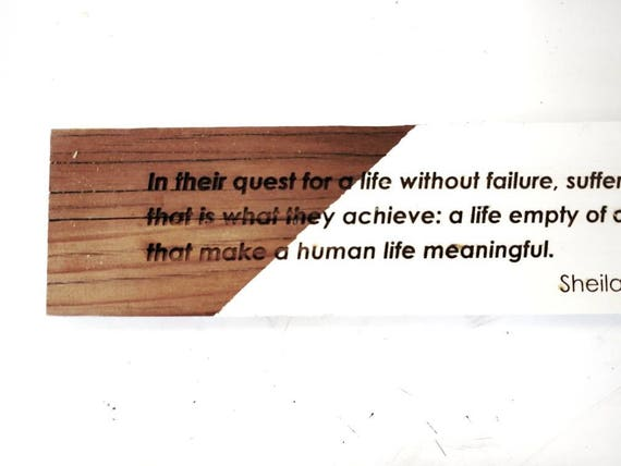 "Sheila Heti engraved on redwood ""In their quest for a life without failure, suffering, or doubt, that is what they achieve..."""