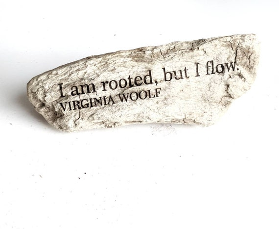 "Virginia Woolf quote ""I am rooted but I flow"" engraved on driftwood."
