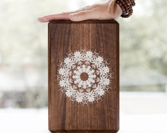 Yoga block hand made from walnut. The print is white representing a mandala. All the blocks are cover whit 3 layers of water varnish.