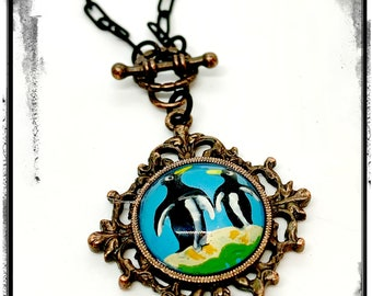 Pretty reverse hand painted glass Penguin cameo set on a rusted iron bezel with a match bail, and a matte black paperclip chain and clasp.