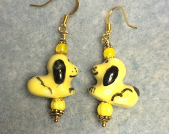 Yellow and black ceramic puppy dog dangle earrings adorned with yellow Czech glass beads.