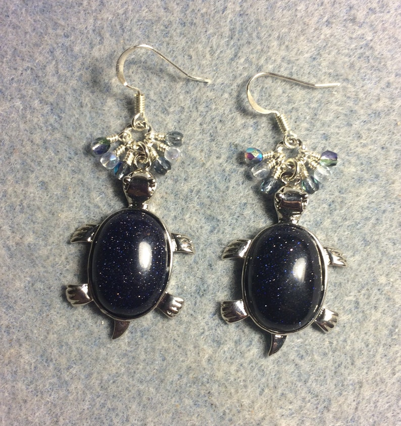 Silver and blue goldstone gemstone turtle charm earrings adorned with tiny dangling blue Czech glass beads.
