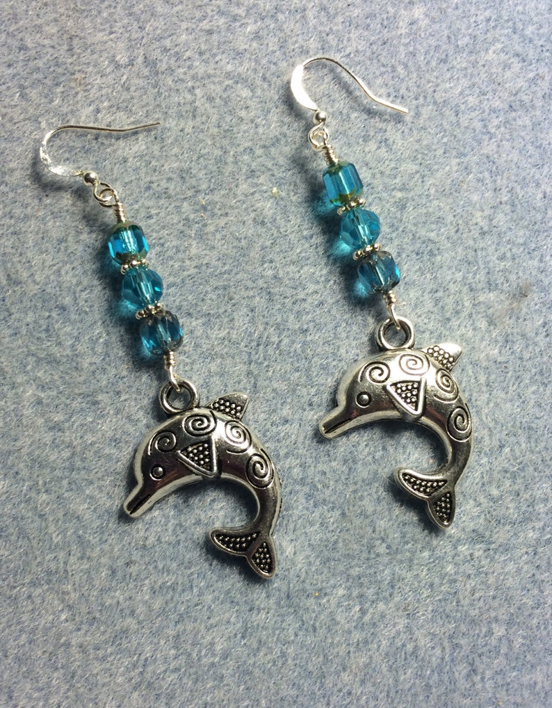 Silver dolphin charm dangle earrings adorned with turquoise Czech glass beads.