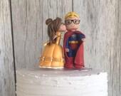 Belle Kissing Blonde Superman Both with Nerd Glasses Wedding Cake Topper