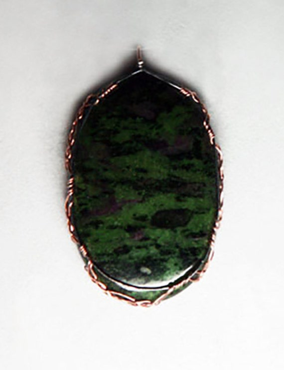 Ruby zoisite cabochon wrapped Celtic style in silver and gold