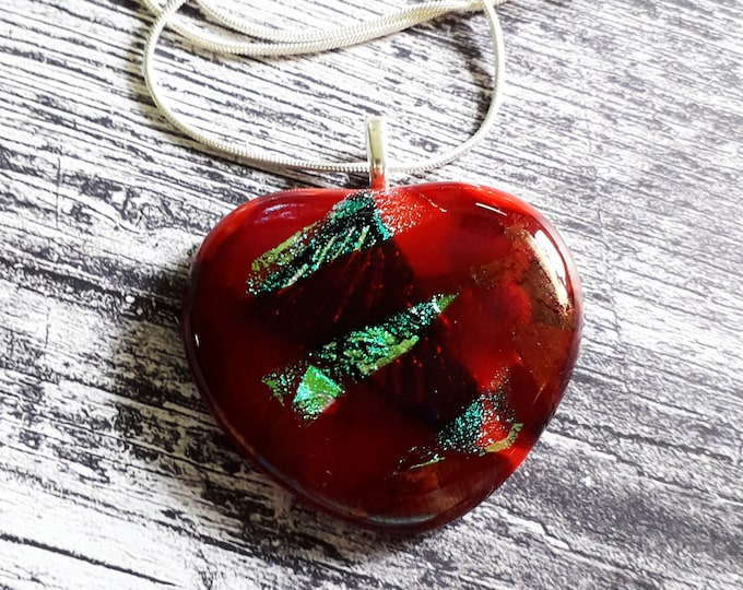 Heart pendant, in a mix of red, dichroic, and iridescent cast glass.