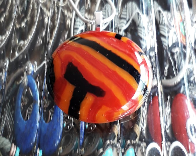 Cast glass pendant, in red, orange and black.