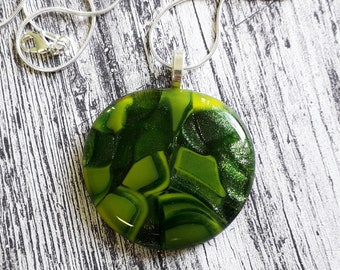 Cast glass pendant, mix of light, dark, and sparkly greens.