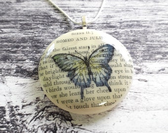 Romeo and Juliet fused glass pendant with butterfly illustration.