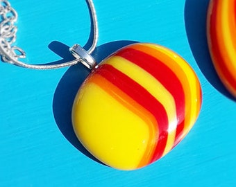 Fused glass pendant in red, yellow and orange opaque glass.