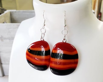 Fused glass earrings, made from orange, black and red fused glass on silver.