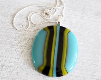 Fused glass pendant in cool green, blue and black colours.