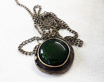Green glass pendant, made from sparkly dark green glass, set in bronze metal.