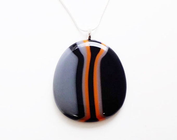 Fused glass pendant in black, grey and orange stripes.