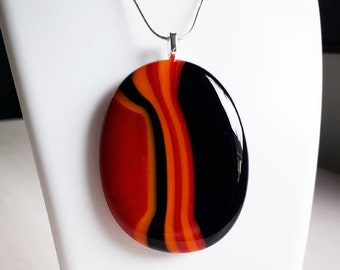 Fused glass pendant, in red, black and orange stripes.