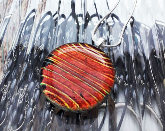 Red dichroic pendant, made from red/gold fused glass with red/gold stripe pattern.