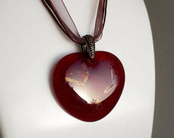 Red heart pendant, dark red cast glass with iridescent and dichroic highlights.