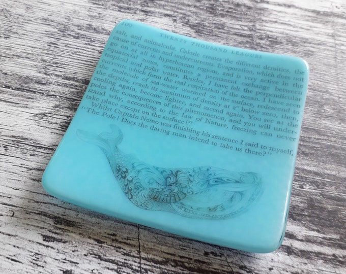 Whale trinket dish, with text from Jules Verne's 20000 Leagues Under The Sea, on blue fused glass.