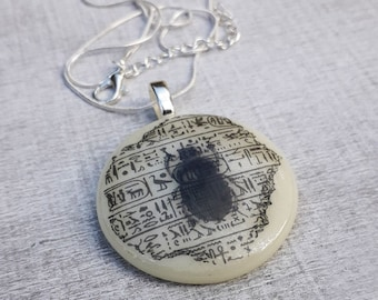 Fused glass pendant with scarab and hieroglyphs print in blacck on cream coloured glass.