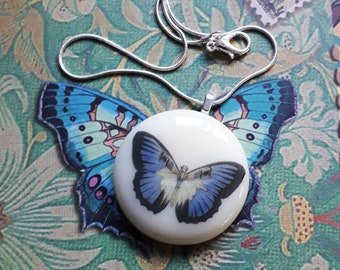 Fused glass pendant with vintage style butterfly illustration in blue and black.