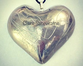 Large silver heart pendant with an adjustable leather thong.