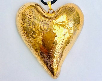 Large gold heart pendant with an adjustable cotton cord.