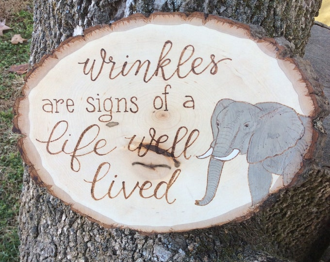 Wrinkles are signs of a life well lived woodburned and water colored wood slice