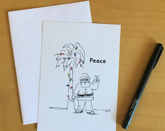 The Peace Santa Holiday Card Pack is a custom illustration of a cool Santa flashing the peace sign under a decorated palm tree