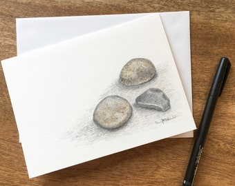 Three small river rocks drawn in layers of colored pencil on 140lb watercolor cardstock make a unique way to celebrate Autumn.