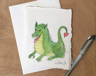 """Send your love with this cute green dragon with a heart-shaped tail. A  Watercolor card, approx. 4.5""""x6"""". Spread love with mailable art!"""