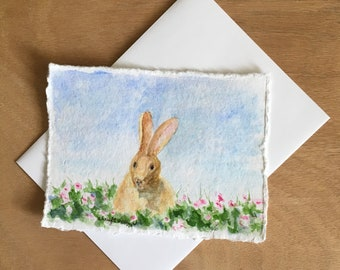"""Little Brown Easter Bunny sits is a field of pink flowers. Hand-painted watercolor card approx. 4.5""""x6""""."""