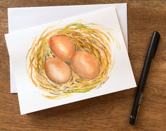 """Three Brown Eggs in a nest, a symbol of new life for Spring and Easter.  Hand-painted watercolor card  5""""x7""""."""