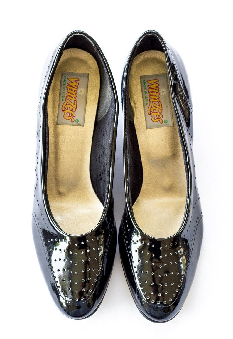 Black patent leather brogue pumps with low heel