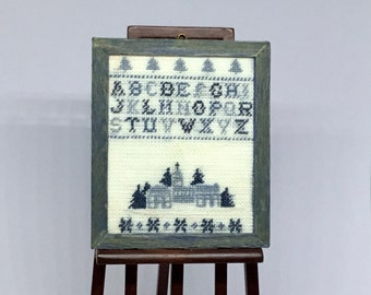 Miniature sampler for dollhouse, with alphabet embroidered on linen.