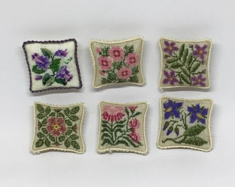Miniature dollhouse pillow, with small dot flower embroidery on linen canvas.